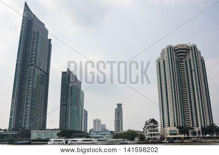 BANGKOK THAILAND - JANUARY 25 2015: Skyscrapers along Chao Phraya River in Bangkok. Chao Phraya river is a major river in Thailand