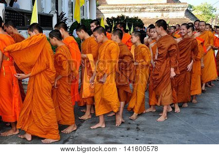 Chiang Mai Thailand - December 19 2012: Barefooted novitiate teenage monks wearing orange robes enter the ubusot sanctuary hall for morning prayer at Wat Chedi Luang