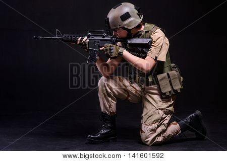 Girl in helmet aiming from gun on black background