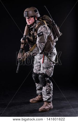 US ranger in helmet and body armor with gun on dark background