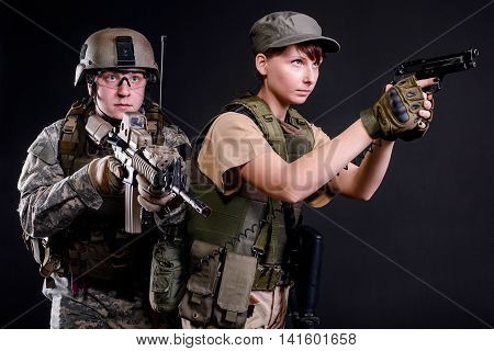 Young husband and wife in military uniform with guns on dark background
