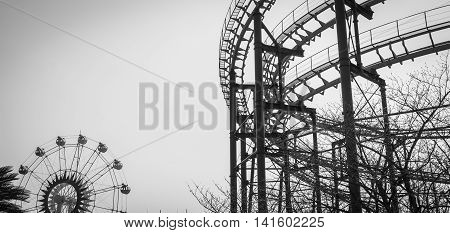 Roller coaster track structure and ferris wheel silhoette