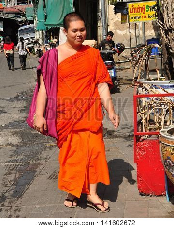 Chiang Mai Thailand - December 23 2012: Young Buddhist monk iwearing an orange robe walking to the Pung Tao Gong Chinese Ancestral Temple
