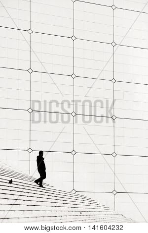 PARIS, FRANCE - MAY 13: Pedestrian and pigeon in la Defense business district on May 13, 2015 in Paris. With the population of 2M, Paris is the capital and most-populous city of France.