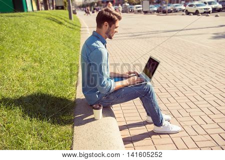 Happy Young Man Sitting On Parapet And Chatting On Laptop