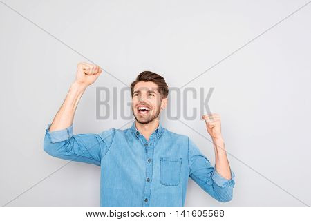 Portrait Of Glad Man Celebrating Victory With Raised Hands