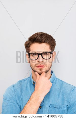 Portrait Of Ponder Smart Man In Glasses Touching Chin