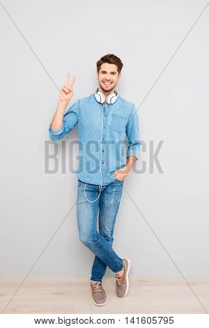 Full Length Portrait Of Happy  Man  With Headphones Showing Two Fingers