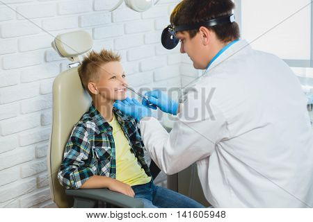 Ent doctor or Otolaryngologist examining a kid nose.