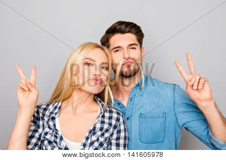 Portrait Of Funny Man And Woman Making Mustache From Hair And Gesturing With Two  Fingers