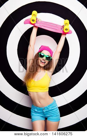 Happy Slim Fit Girl In Spectacles Holding Raised Skate