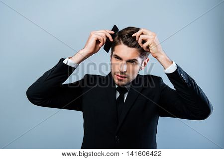 Portrait Of Handsome Young Businessman Combing His Hair