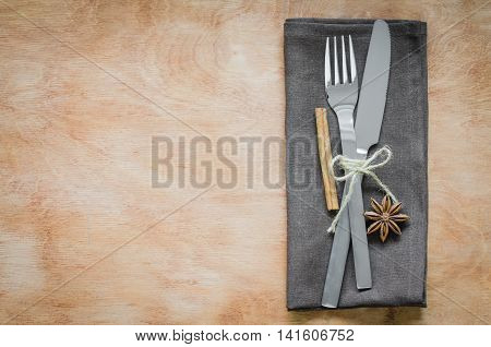 Close up Fork and Knife Tied on Brown Napkin Styled with cinnamon and anise on Wooden Table with Text Space.