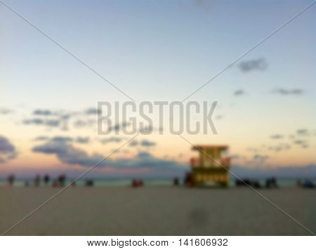 Abstract blurred beach background with colorful cloud and blue sky. People near lifeguard tower watching sunset at the beach.