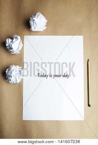 Crumpled up papers with a sheet of blank paper and a pencil on brown background, today is your day