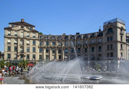 MUNICH, GERMANY - AUGUST 29, 2015: Stachus fountain on Karlsplatz in Munich with view to the curved building towards the inner city unidentified people are walking along