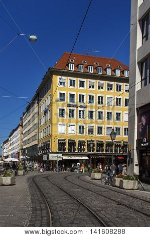 MUNICH, GERMANY - AUGUST 29, 2015: The Roeckl House in the inner city of Munich at the crossing of Perusastrasse and Theatinerstrasse unidentified people are walking around for shopping