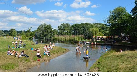 DEDHAM, ESSEX, ENGLAND - AUGUST 06, 2016: People paddling in the river Stour on the Suffolk -  Essex border enjoying the summer sunshine.