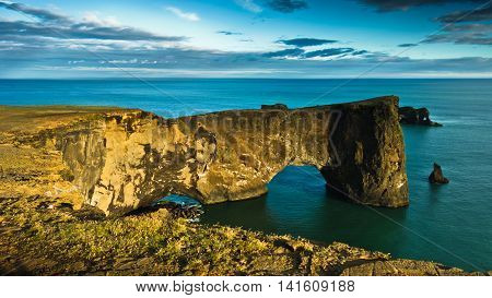 Magnificent rock arch at Dyrholaey, Iceland. Dyrholaey means the hill island with the door hole. It is 120 m high and you are able to walk the arch or the bridge if you are not afraid