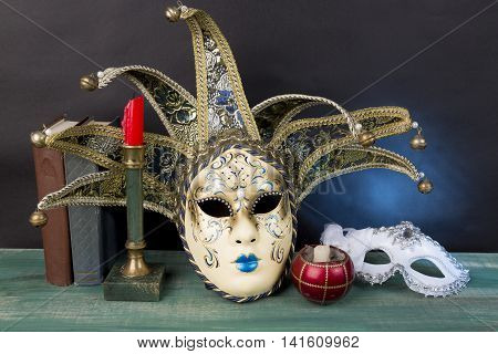 Art concept. Venetian carnival masks with vintage books and candlesticks on green wooden surface against dark background.