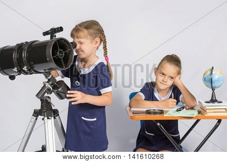 Girl Astronomer Looks Through The Eyepiece Of The Telescope, The Other Girl Thinking Waiting For The