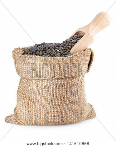black lentils with wooden scoop in burlap bag isolated on white background.Super food