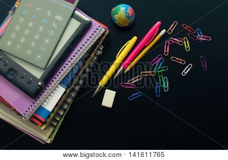 Back to school concept. School supplies with calculator and ebook on blackboard background with space for text. Back to school concept with stationery. Schoolchild studies accessories. Top view.