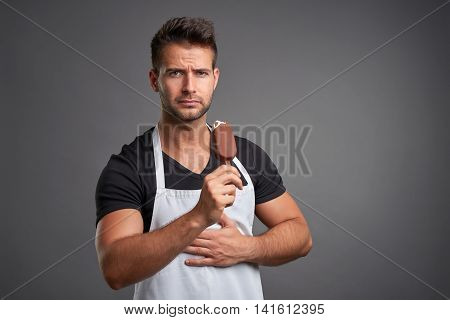 A handsome young barista man having a stomach ache while eating an ice-cream