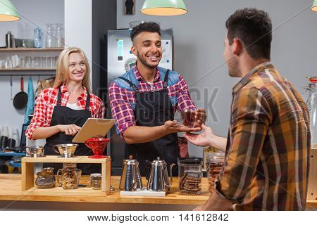 Barista serving client give glass tea coffee shop bar counter, mix race man and woman happy smile to customer