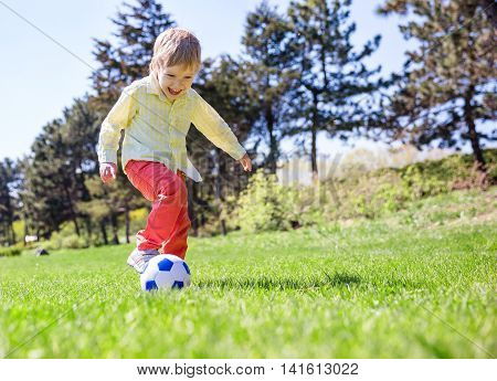 Happy young boy playing football outdoors in summertime