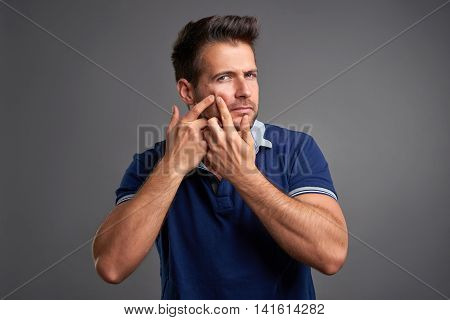 A handsome young man checking and squeezing a spot on his face