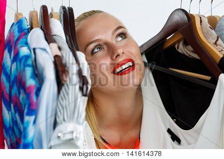 Beautiful Blonde Woman Standing Inside Wardrobe Rack