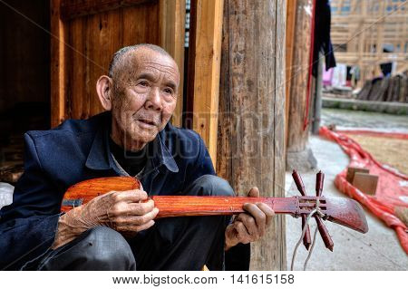 Zhaoxing Dong Village Guizhou Province China - April 9 2010: Elderly Asian men peoples Dong playing at the local stringed musical instruments sitting on the threshold of a wooden farmhouse.