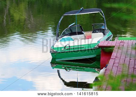 Motor boat moored by the pier in silent place with beautiful nature