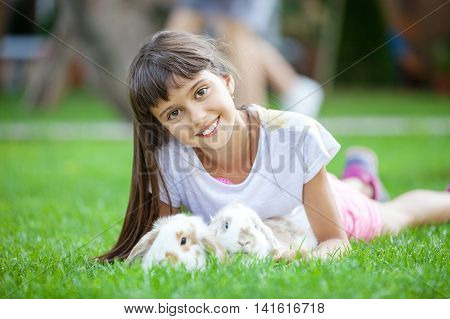 Smiling girl with pet rabbits on green grass in park