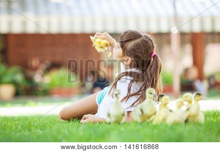 Cute girl lying down on grass and holding spring duckling