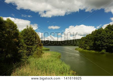View of the canal and Karsińskie lake in summer under blue sky and white clouds. Small village Swornegacie Bory Tucholskie Poland. Horizontal view.