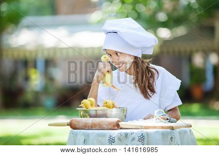 Smiling little chef holding ducklings while cooking outdoors