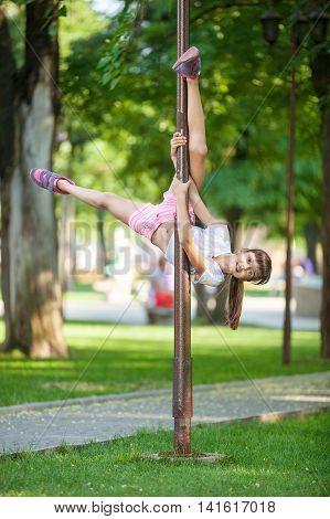 Cute girl having fun outdoor using a street lamp as a gymnastic pole