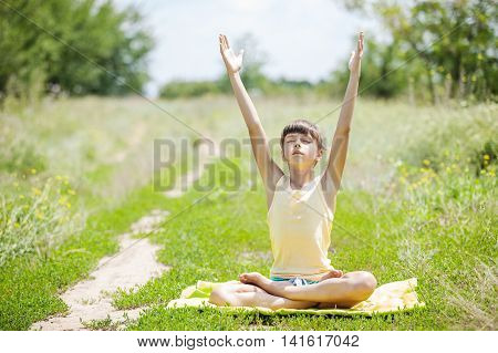 Little girl relaxing while sitting in lotus positionon on grass.