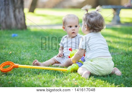 Baby boy and toddler girl playing while sitting on green grass in park