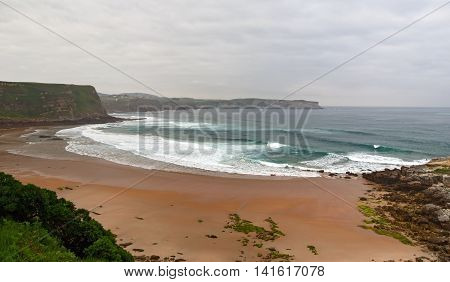 View of the sandy beach in cloudy foggy day. Spain suburb of Suances summer day in the Province of Cantabria it is photographed from Playa de Los Locos.