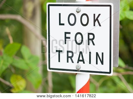 Look for train warning sign black lettering on white background.
