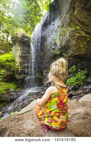 Littlei girl sitting next to idyllic tropical waterfall