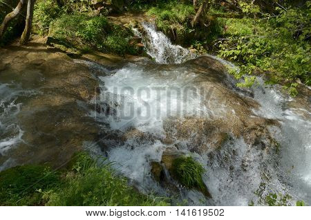 Water of a fast mountain river flowing down the mountain creating cascades