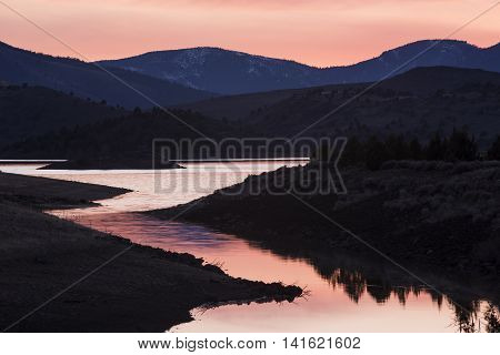 Pink sunset in Weed California lake by Mount Shasta with hills and meadows