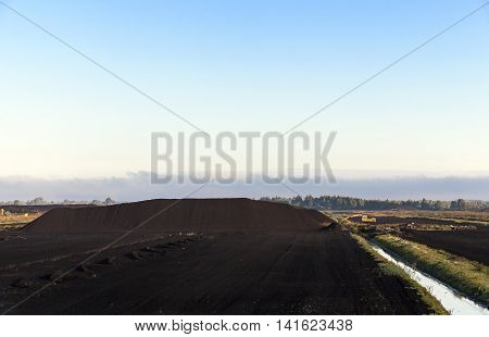 bog and the field on which the production is carried out in black peat mining, industry, old tractor