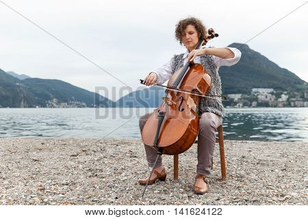 beautiful girl plays the cello at the seaside