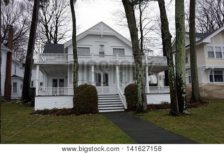 A white home, with a wraparound front porch and balcony, on Beach Drive in Wequetonsing, Michigan.