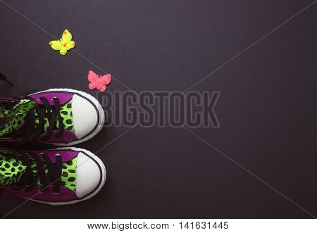 Violet sneakers with leopard print on black board vintage filter; copy space
